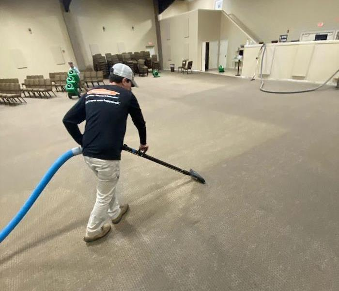SERVPRO tech with extraction wand and wet gray carpet