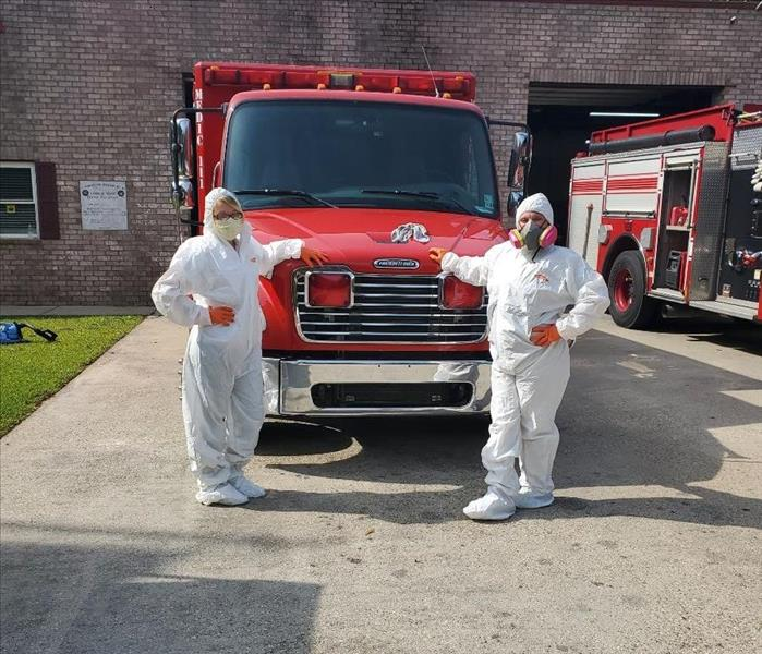 two employees posing in white Tyvek suits in from of a fire truck