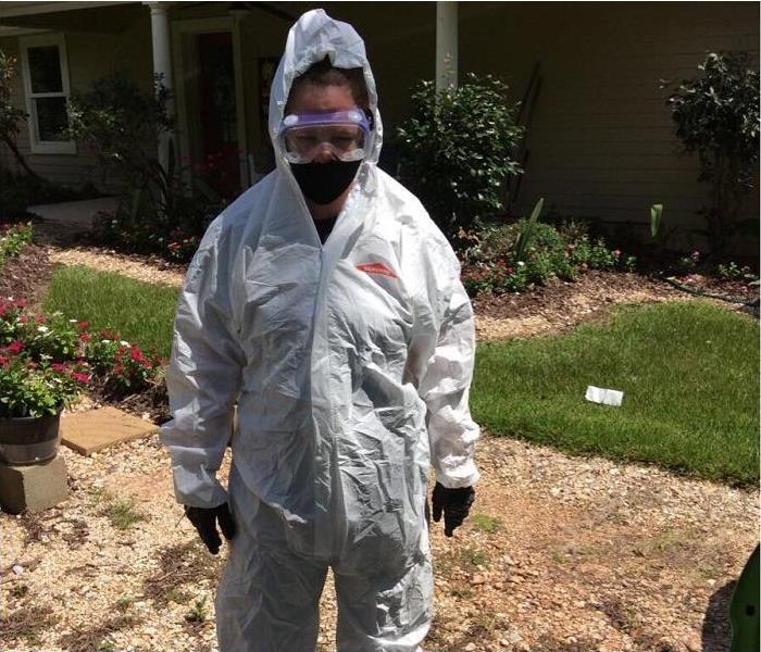 SERVPRO tech, donned in PPE, stanading in front of home
