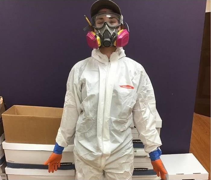 SERVPRO tech, donned in PPE standing in hallway of office; boxes in background