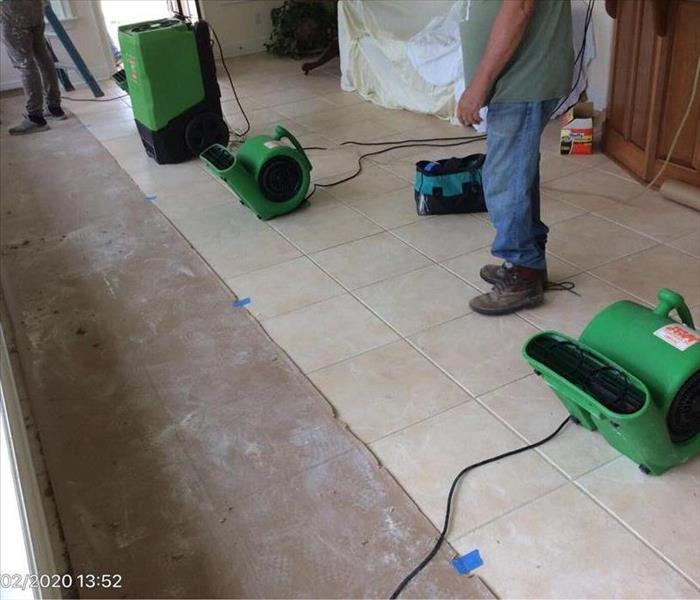SERVPRO tech with drying equipment on the tile floor