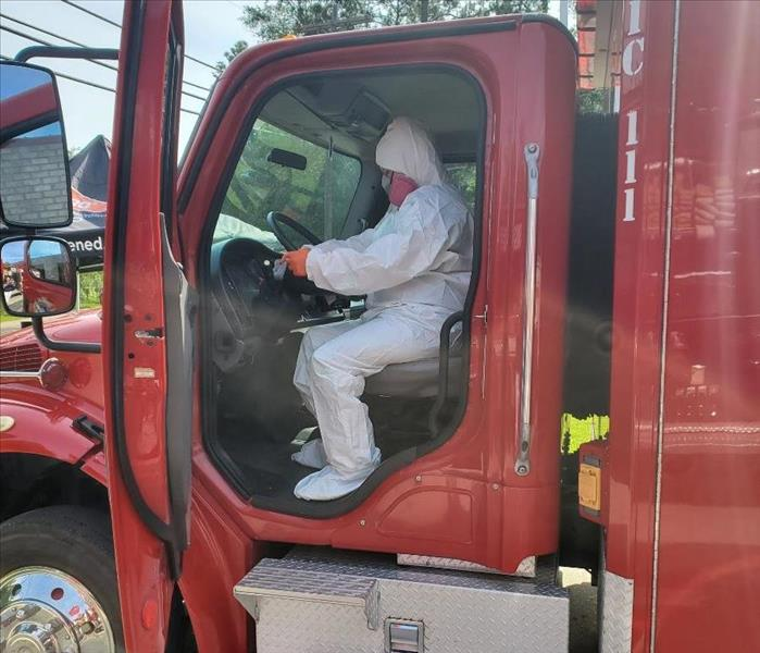 worker, dressed in white Tyvek suit is cleaning a steering wheel in an ambulance