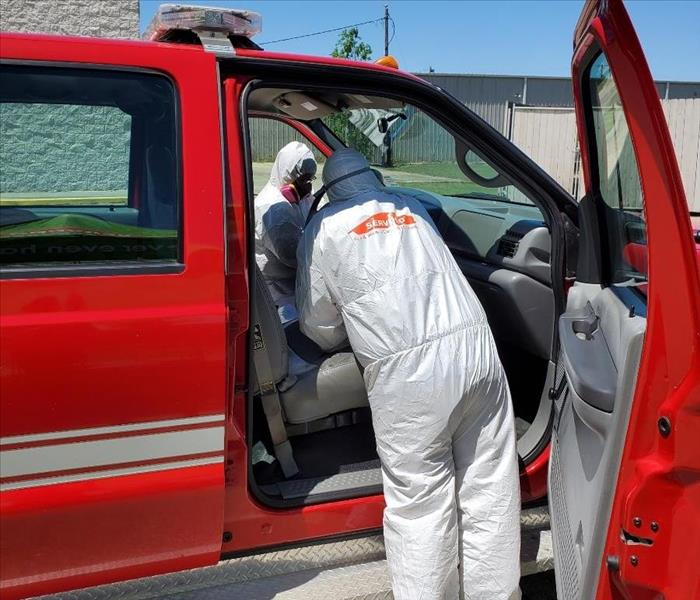 two SERVPRO employees in white protective suits cleaning a red vehicle