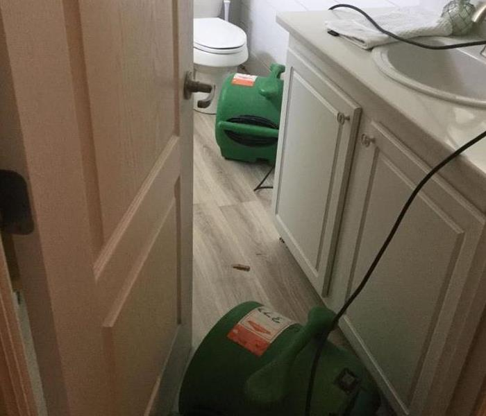 A bathroom with SERVPRO equipment on the floor.