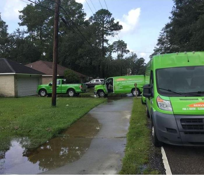 SERVPRO vehicles parked in front of home with flooding