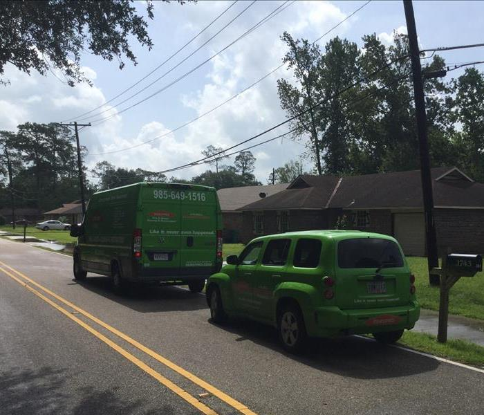 Two SERVPRO vehicles on the street in front of a home.