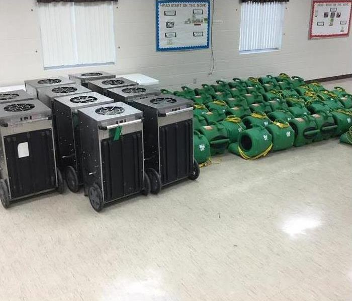 Rows of our drying equipment and air movers in a room ready to be used